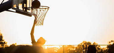 basketball player making a shot with sunset in the background