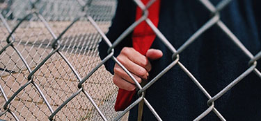 chain link fence with a student standing behind it
