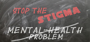 Chalk board with the words Stop the Stigma and Mental Health Problem crossed out