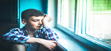 teenage boy sitting next to a window look sad