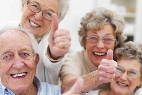 Group of seniors giving a thumbs up gesture